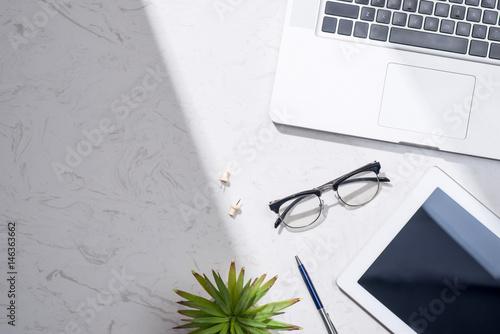 Flat lay, top view of laptop, digital tablet, eyeglasses and pen.