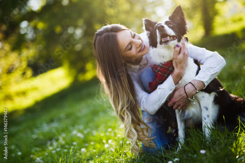 Poster Beautiful woman walking cute dog in nature