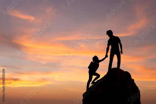 Teamwork couple hiking help each other trust assistance silhouette in mountains, sunset Poster