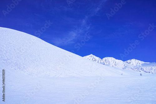 スキーゲレンデとシュプールと雪山