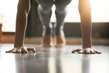 Young woman practicing yoga, doing Push ups or press ups exercise, phalankasana Plank pose, working out, wearing sportswear, grey pants, indoor, home interior, living room floor. Close-up of hands - 146575809