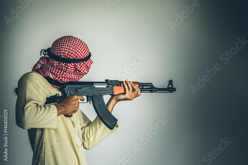 Muslim Robber holding a gun at abandoned building Poster