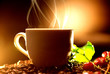 Coffee. Cup of steaming coffee with the real coffee ripe berries, flowers and leaves on a branch of coffee tree over wooden background, silhouette