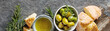 Leinwanddruck Bild - Olivier oil with fresh herbs and bread. Gray background. Italian and Greek national food. Top view