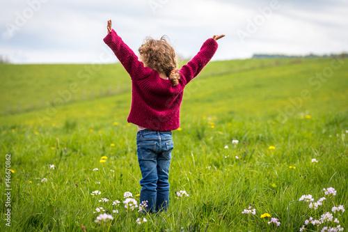 une petite fille levant les bras au milieu d'un pré