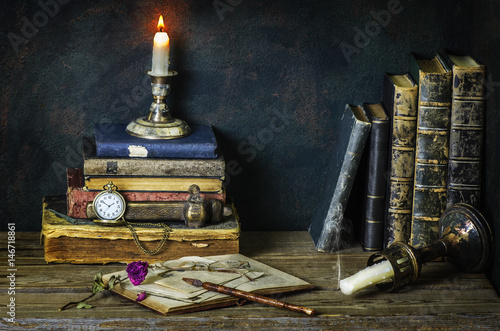 Classic still life with vintage books placed with pocket watch,illuminated candle,letters,inkwell and dry flower on rustic wooden background