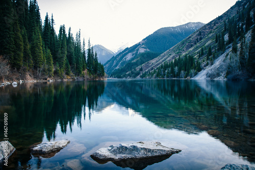 Majestic blue mountain lake with green trees - 146769809