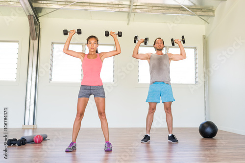 Póster Fitness couple working out together training arms doing overhead shoulder press with dumbbells weights standing dumbbell press exercise at gym