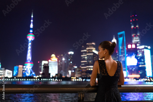 Elegant asian woman in evening dress relaxing by the Bund river in Shanghai looking at the night city lights of Pudong skyline Poster