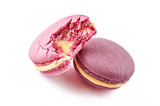 Two colorful French almond cookies macarons or macaroons isolated on white background. One cookie is bitten. Front view.