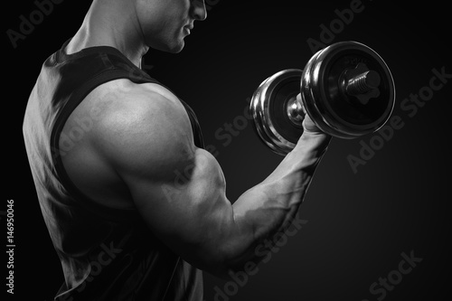 Black and white photo of handsome power athletic man in training pumping up muscles with dumbbell. Close-up of a power fitness man.