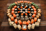 Great appetizing sushi set, food art. Fresh colorful round ornament of rolls served on brown straw mat, closeup. Japanese seafood, restaurant menu photo.