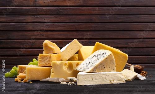 Fototapeta Various types of cheese on black wooden table.