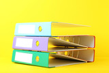 Colorful office folders on yellow background