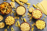 Different kinds of pasta in bowls on grey table - 147054608