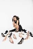 Inside the Studio woman in black dress with gorgeous long dark hair among the shoes. - 147086884