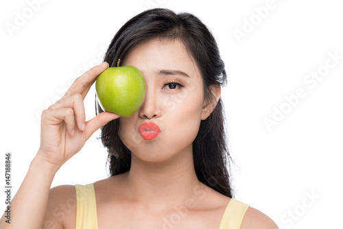 Pretty young asian woman holding fresh apple isolated on white background.