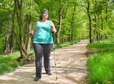 Overweight woman walking on forest trail. Slimming and active lifestyle theme.  - 147253834
