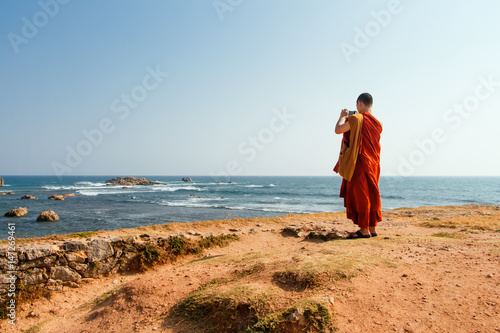 A Buddhist monk at Fort Halle in Sri Lanka takes pictures of the ocean Poster