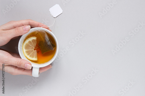 Papiers peints The Tea time. Hands holding cup of hot black tea on the blue background, top view