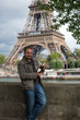Attractive young man holds champagne in center of Paris