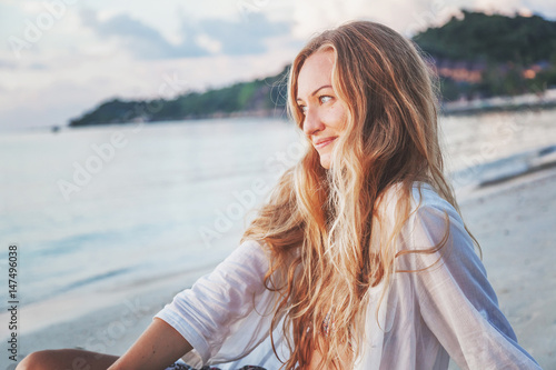 Portrait of an attractive young woman with long hair on the sea shore