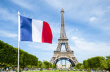 French flag flying in bright blue sky above the Eiffel Tower in Paris, France