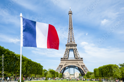 French flag flying in bright blue sky above the Eiffel Tower in Paris, France Poster