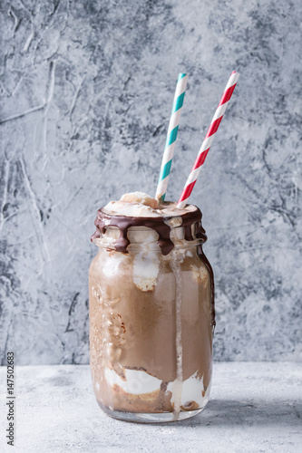 Papiers peints Lait, Milk-shake Chocolate coffee milkshake with ice cream scoop served in glass mason jar with retro cocktail tubes on gray texture background. Summer sweet drink
