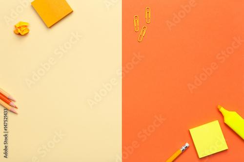 Akcesoria biurowe na żółtym i pomarańczowym tle