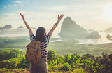 Fototapety Happy young traveler woman backpacker raised arm up to sky enjoying a beautiful of nature at top of mountain and sea view,Freedom wanderlust concept