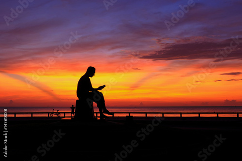 Poster Silhouette sunrise with man read book statue