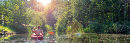 Foto Murales Girl in a kayak and sunny weather, panorama