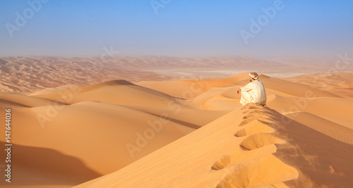 Fotobehang Abu Dhabi arab man in traditional outfit sitting over a Dune in arabian desert and enjoying the peaceful landscape of the empty quarter