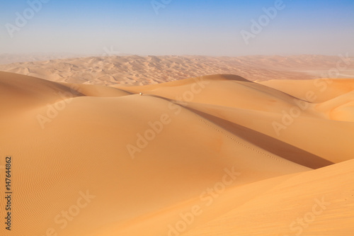Arab man in traditional outfit sitting on a dune in the empty quarter of the arabian Desert