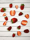 Photo of a strawberry on a white background. Whole and cut berries. Romantic country atmosphere.