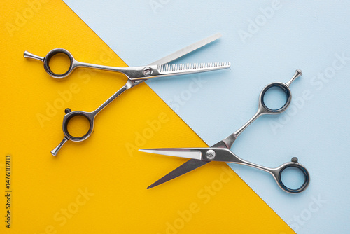 Two sets of stainless steel hairdressing scissors arranged horizontally and para Poster