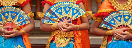 Aluminium Bali Asian travel background. Group of beautiful Balinese dancer women in traditional Sarong costumes with fans in hands dancing Legong dance. Arts, culture of Indonesian people, Bali island festivals.