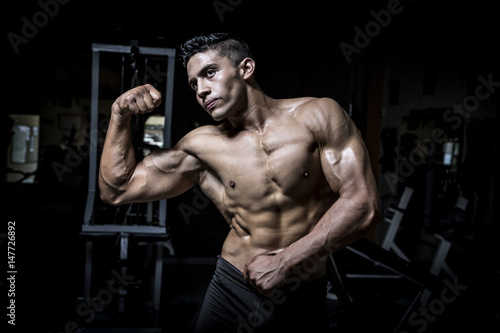 Young man exercising in dark and old gym