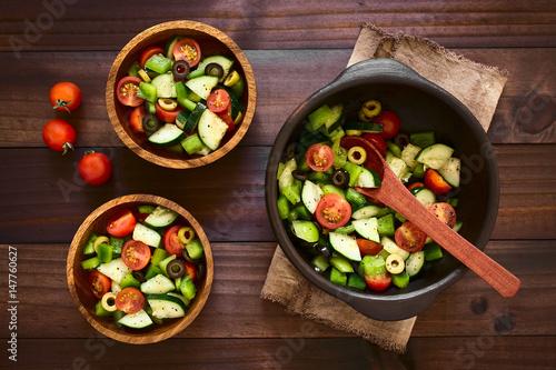 ensalada-fresca-de-aceitunas-negras-y-verdes-tomates-cherry-pimiento-verde-y-pepino-sazonados-con-sal-pimienta-oregano-seco-y-albahaca-fotografiados-sobre-madera-oscura-con-luz-natural