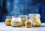 Assorted cereals in glass jars: kinoa, bulgur, couscous, orzo, brown rice, selective focus - 147864068