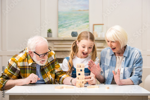 Happy preteen girl with grandfather and grandmother playing jenga game at home плакат