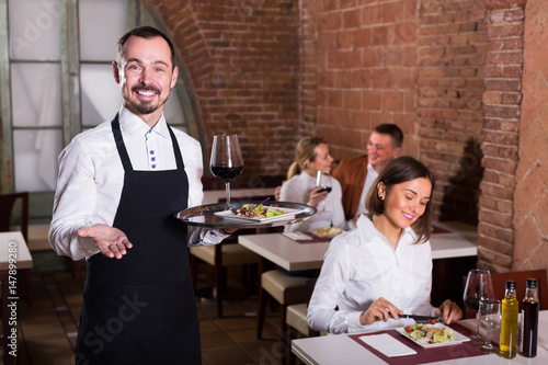 friendly man waiter demonstrating country restaurant