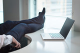 Lazy office worker with feet and socks on table. Useless and relaxing man doing nothing or taking break from work in workstation. Businessman resting during workday. Laziness and relax concept.