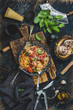Italian style pasta dinner. Spaghetti with tomato and basil in plate on wooden board and ingredients for cooking pasta over dark blue plywood background, top view, vertical composition - 147953483
