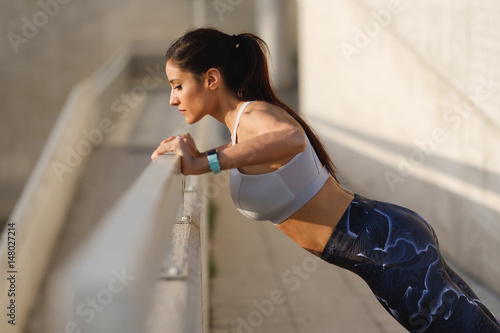 Sporty young woman doing push up strength exercise during urban outdoor fitness workout.
