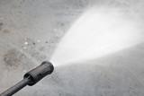 Water hose spray gun washing his cement floor - 148060610