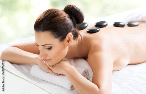 Beautiful, young and healthy woman in spa salon. Massage treatment over green summer or spring background. Traditional medicine and healing concept.
