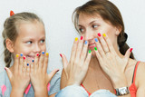Hands of mother and daughter manicure.