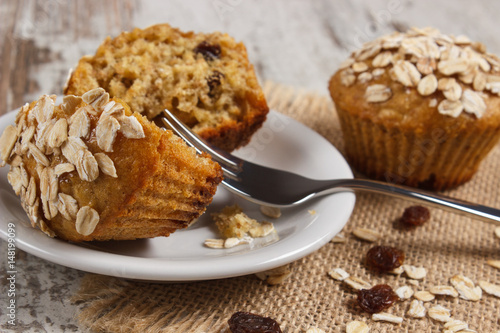 Fresh muffins with oatmeal baked with wholemeal flour on white plate, delicious  Poster